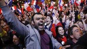 Anhängare till mittenkandidaten Emmanuel Macron firar valresultatet i den första omgången av det franska presidentvalet den 23 april 2017.