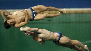 Jack Laugher och Chris Mears mitt i ett simhopp.