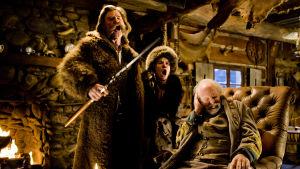 Kurt Russel och Jennifer Jason Leigh skrålar och Bruce Dern håller för öronen.