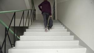 Nuori nainen käytävän portaissa.
