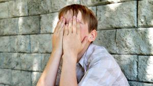 Ett barn gömmer sitt ansikte i sina händer.