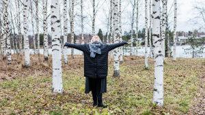 Elina Koskelainen seisoo koivujen keskellä kädet levällään ja katse ylös puiden latvaan.