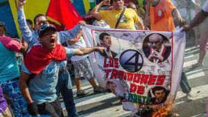Aktivister bränner flaggor med bilder av politiker i Peru som anklagas för att förrått ursprungsfolket i Loreto eftersom de tillät privata oljebolag i området