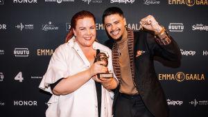 Nana Simelius ja Mikael Gabriel iloitsevat Emma-gaalan promoseinän edessä Vuoden musiikkivideo -palkinnosta.