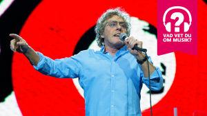 Roger Daltrey håller i en mikrofon med vänster hand och sjunger iden samtidigt som hans högra arm är utsvängd. åt sidan.