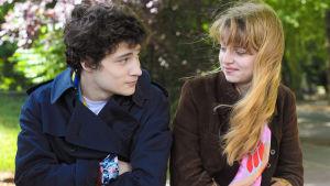 Tyttö ja poika istuvat puistossa lähikuvassa ja katsovat toisiaan.