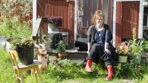 En kvinna klädd i mörka kläder och röda gummistövlar. Hon sitter på trappan till ett rött trähus. Bredvid henne ligger en svart katt och vilar.
