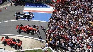 Två Ferrari och en Mercedes står parkerade framför publiken på Silverstone