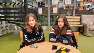 Två flickor sitter vid ett runt bord.