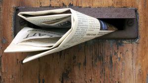 Tidning sticker ut ur postlucka i trädörr.