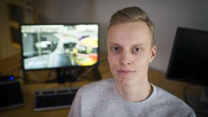 En ung man med kort ljust hår. I bakgrunden syns en datorskärm.