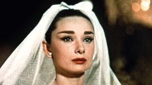 Audrey Hepburn lähikuvassa valkoisessa hunnussa ja silmät kyynelissä. Kuva elokuvasta Rakastunut Pariisissa.