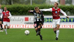 Jani Virtanen smiter undan Toni Huttunen i fotbollsligan 2005.