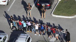 Elever tågar ut från skolan i rad med händerna på varandras axlar.