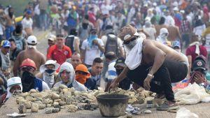 En demonstrant gör sig redo att kasta sten under sammandrabbningarna med säkerhetsstyrkorna vid gränsen mellan Venzuela och Colombia.