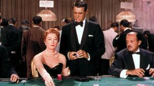 Nainen ja kaksi mies casinon pelipöydän äärellä.