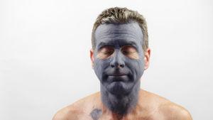 en medelålders man med en ansiktsmask av lera. Skönhetsbehandling.