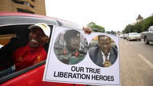 """""""Våra verkliga befrielsehjältar"""" står det på den här demonstrantens plakat. Fotografierna på plakatet visar arméchefen Constantino Chiwenga och den avsatte vicepresidenten Emmerson Mnangagwa."""