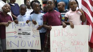 Barn deltar i demonstration där man ber att myndigheterna förnyar åppehållstillstånden för personer från Haiti och andra Latinamerikanska länder