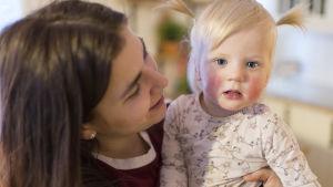 En kvinna sitter med en liten flicka i famnen.