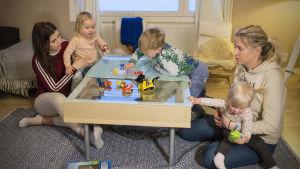 Till vänster i bilden sitter en kvinna som håller en flicka som spelar Kimble med sin äldre bror. Till höger en annan kvinna med en liten flicka i famnen.