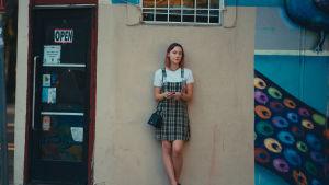 Lady Bird står lutad mot en vägg.