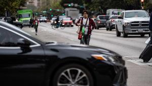 En man i glasögon och med en sparkcykel står i en korsning på en gata i Austin i Texas. Framför honom ses en bil. Bakom honom bilar och en kvinna på sparkcykel.