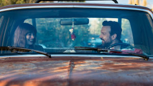 Nainen ja mies istuvat autossa ja hymyilevät toisilleen.
