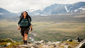 En kvinna iklädd vandringskläder och ryggsäck kommer gående över fjället. I bakgrunden syns berg.