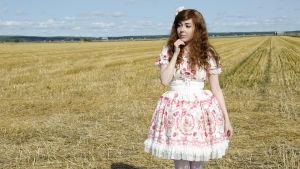En kvinna klädd i så kallade Lolitakläder - en fluffig vit och rosa klänning med spetsar på. Hon har vita högklackade skor och blommor i håret. Hon står på en nyklippt åker.