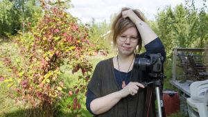 En kvinna står och lutar sig mot en kamera som står på ett stativ. Hon står i en trädgård. Det är sensommar.