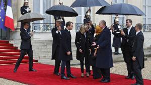 Presidentparet Macron tar emot statschefer vid presidentpalatset.