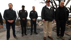 Donld Trump med följe studerar skogsbrandens härjningar i Kalifornien.