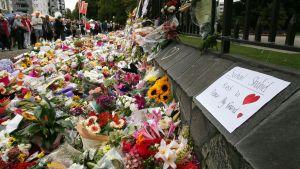 Ett berg av blomster vid en av minnesplatserna i Chrischurch.