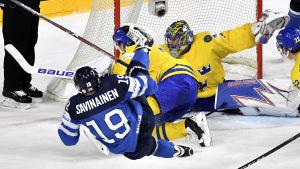 Henrik Lundqvist räddar ett skott av en fallande Veli-Matti Savinainen.