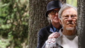 Kaksi miestä seisoskelee puun takana.