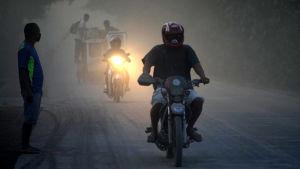 En man åker motorcykel i askan.