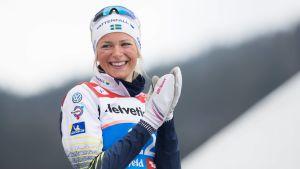 Frida Karlsson ler på prispallen.