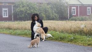 Emilia Jansson står på en väg tillsammans med sin hund och en av sina katter.