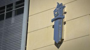 närbild av polisemblemet svärd med lejonhuvud på fasaden av Vasa polishus