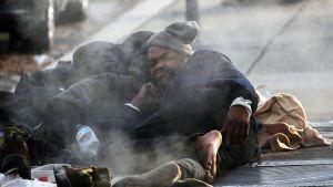 Man i Washington, USA värmer sig ovanpå en gatubrunn.