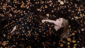 Wilma Hurskaisen teos Autumn: nainen makaa maassa syksyn lehtien keskellä