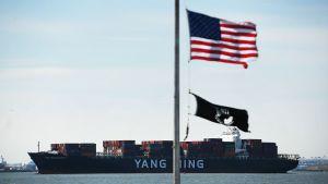 Kinesiskt fullastat continerfartyg anländer till New Yorks hamn. USA:s flagg i förgrunden.