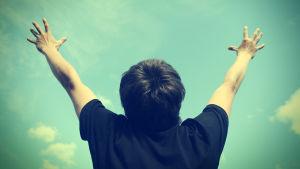 Ung man står med händerna uppsträckta mot himlen.