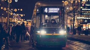 Ratikka ottaa matkustajia kyytiiin illan pimeydessä.