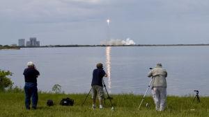 Fotografer på strand ser uppskjutning av Falcon 9-bärraketen i stort rökmoln på Cape Canveral