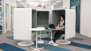 En kvinna jobbar vid en dator i ett kontor.