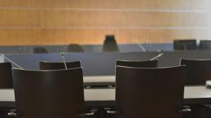 tomma stolar i en rättssal med det tomma domarbordet oskarpt i bakgrunden