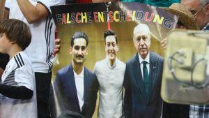 Kritiska fotbollsfans håller upp en skylt med en bild på Mesut Özil där han poserar med Turkiets president Recep Tayyip Erdogan.