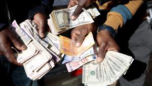 Svarta marknaden för valuta blomstrar i Zimbabwe. Valutahandlare visar upp stora mängder dollar och andra utländska valutor i Harare.